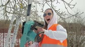 nag : Mad young girl in a yellow vest screams and swings a chainsaw. Concept: crazy woman-saw