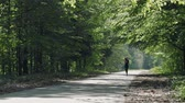 girlish : Young brunette with headphones running on a forest road. HD