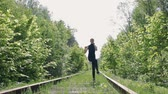 girlish : Young brunette in a black suit performs physical exercises on the background of an abandoned railway. Steadicam shot Stock Footage