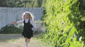 backtoschool : Portrait of a blonde schoolgirl 1-2 class with a portfolio. Girl in school uniform in a hurry to class Stock Footage