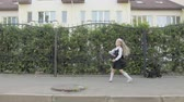 backtoschool : Little funny schoolgirl in school uniform and briefcase on his shoulders walking around the area. In the hands of the girl rainbow spinner, near the road is a cat. Steadicam shot Stock Footage
