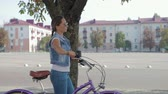 sonhador : Image of a beautiful, young girl with a pigtail, in a denim suit and sunglasses, who walks leisurely down the street with a glass of coffee and rolls a purple Bicycle.