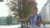 disposable cup : Image of a beautiful, young girl with a pigtail, in a denim suit and sunglasses, who walks leisurely down the street with a glass of coffee and rolls a purple Bicycle.