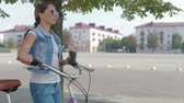 bisiklete binme : Image of a beautiful, young girl with a pigtail, in a denim suit and sunglasses, who walks leisurely down the street with a glass of coffee and rolls a purple Bicycle.