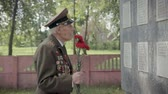 An elderly gray-haired veteran of the great Patriotic war and world war II in uniform with many badges and orders stands near the monument. My grandfather is in the hands of red carnations. Steadicam shot