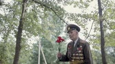 An elderly gray-haired veteran of the great Patriotic war and world war II in uniform with many badges and orders goes to the monument. Grandpa is in the hands of red carnations. Steadicam shot