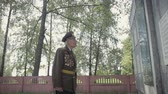 An elderly gray-haired veteran of the great Patriotic war and world war II in uniform with many badges and orders stands near the mass grave. The grandfather remembers horrors of military operations, destruction and death of people. Steadicam shot