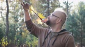 janota : City hipster with glasses and braided leaves in his beard, shows his braid on his chin. It stands against the autumn forest. 4K Stock Footage
