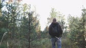 turisté : The guy slowly walks in the autumn forest and enjoys nature, wearing a jacket and jeans on his back hanging backpack. Hiking in the forest, taiga