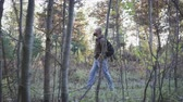 mochila : A handsome, bearded young man with a backpack on his back walks through the forest, breathes fresh air and enjoys the autumn landscape Archivo de Video