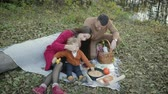 torten : Beautiful, stylish, young family resting on a picnic by the river, autumn landscape. Warm weather