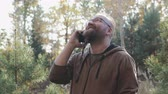 разговор : Bearded man with glasses talking on the phone fun in the Park, against the autumn landscape