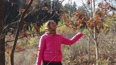 eşarp : A young, rural girl in a scarf and a pink jacket enjoys a yellow leaf fall and catches leaves in the autumn forest. Sunny day