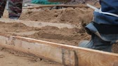 pala : Men workers align wooden plank and tamp sand with gravel for pouring concrete screed under the floor on the ground