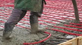 su tesisatı : Steadicam shot of builders performing the pouring of the concrete screed floor heating on the ground from the spray machine