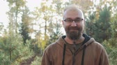 janota : Portrait of a bald man with glasses and a beard, who rejoices against the autumn forest Stock Footage