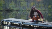 dusk forest : The General plan of two people, mother and son sitting and playing in the fresh air, on the pier near the forest lake. Around Sunny autumn weather Stock Footage