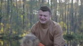 tossing : Portrait of a young, happy family having fun playing in a forest Park outdoors. Father holds carefree son in his hands and throws up Stock Footage