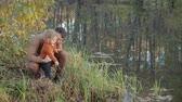 paternidade : Happy, young father spends time on the shore of a forest lake with a beautiful, small, blond son. The water reflects the trees. The boy hits the water with a stick. Concept of family Vídeos