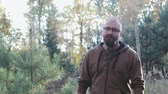 janota : Brutal, bearded, bald man with glasses goes to the camera forward against the autumn forest Stock Footage