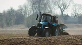 vyrobit : Static shot of a blue tractor with big black wheels and a powerful grouser, heavy plowing the dark fertile soil. The warmth from the ground and the motor distorts the image Dostupné videozáznamy