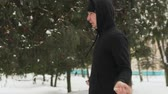 adolescente : Steadicam shot of a young guy in a black tracksuit performing exercises, jumping rope in a snow-covered Park outdoors in frosty weather. The mans mouth is steaming. The concept of winter sports, healthy lifestyle Vídeos