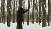 coberto : Steadicam shot is a side view of a young guy in black sportswear and a Balaclava performing a warm-up before training in a winter snow-covered city Park. The concept of hardening fighter, puncher, lover of martial arts
