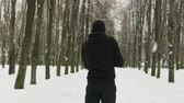 gyalogút : Steadicam shot rear view of a young guy in black sportswear with a hood performing a hand-held workout in a winter snow-covered city Park. The concept of hardening fighter, puncher, lover of martial arts