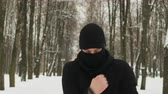 gyalogút : Steadicam shot a front view of a young guy in black sportswear with a hood and a ninja Balaclava performing punches in motion in a winter snow-covered city Park. The concept of hardening fighter, puncher, martial arts lover Stock mozgókép