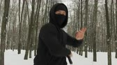 portrait shot : Steadicam shot active young men, a fighter of martial arts, dressed in black with a mask on the person performing the technique of blows with nunchaku in the winter, snow covered city Park among the trees Stock Footage
