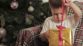 hajópapírok : Happy, little baby sitting under the Christmas tree on the chair at home and opens his gift. Christmas, winter miracles. The concept of new year