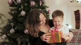 oynak : Happy, smiling mother and child on Christmas tree background. mom gives her son a beautiful gift. Family holiday, new years concept Stok Video