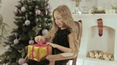 tasavvufi : A little girl with white curls and a black dress opens a Golden box with a gift. She sits in a chair by the fireplace with a Christmas tree. A celebration of the new year