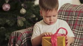 fordulat : Happy, little baby sitting under the Christmas tree on the chair at home and opens his gift. Christmas, winter miracles. The concept of new year