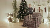 sürpriz : Beautiful baby fun jumping and laughing in the chair for the new year. The room is decorated with lights and balls, there is a Christmas tree Stok Video