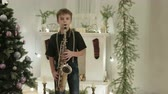 небольшой : Young saxophonist shows his Christmas performance on the instrument. It is in a beautiful, decorated room with a Christmas tree. The concept of new year