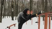 horizontální : Steadicam shot purposeful man in a black tracksuit with a hood, performing the stretching of the leg muscles on the old, vintage the bar. The concept of physical education in the open air in the winter, snow-covered Park Dostupné videozáznamy
