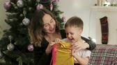небольшой : A young mother and her cute little son unwrap the gift in a bright, Golden package sitting on the couch near the Christmas tree. The boy is surprised and happy. The concept of new year Стоковые видеозаписи