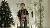 naladit : Young saxophonist shows his Christmas performance on the instrument. It is in a beautiful, decorated room with a Christmas tree. The concept of new year