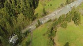caminhadas : Aerial view of the fast-flowing mountain river among the green fir trees on the edge of the forest. Spring Carpathians, The Tatras, The Alps