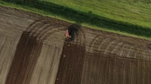 coltivazione : Aerial top view of a red tractor with dual wheels doing the processing brown soil with a disc cultivator, by flying birds. Agricultural sowing campaign the farmers