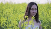 A beautiful woman with dark hair and freckles on her face walks in a large rapeseed field in the summer, moths fly around. Girl enjoying nature
