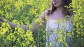 coltivazione : A beautiful woman with dark hair and pigmentation on her face walks in a large rapeseed field in the summer. Girl enjoying nature