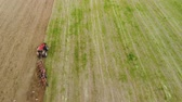 coltivazione : Top view of the tractor with working plow from the drone pov, agricultural machine red color works the soil for planting Filmati Stock