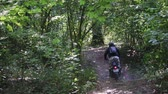 birtok : Slow-motion shot of a man in protective gear with a helmet riding an extreme black Enduro on a forest trail among trees and branches with leaves. The art of owning a motorcycle on rough terrain Stock mozgókép