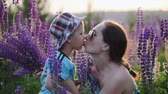 небольшой : Mother in dark sunglasses kisses a cute little boy, a son in a blue t-shirt and patterned hat in a field, against a background of narrow-leaved purple lupine flowers. The concept of motherhood, adoption