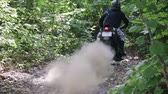 střídat : Athlete in protective gear on a motorcycle Enduro starts, dust and dirt fly from under the wheels. Race in the green forest over rough terrain. The concept of active recreation.