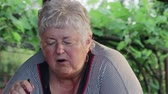 gepensioneerd : Funny short-haired elderly overweight woman is eating an outdoor vegetable salad with a spoon and has a pensive look. The lady is missing a front tooth. Healthy lifestyle concept