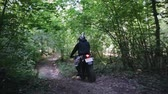 birtok : Motorcyclist in protective gear on black Enduro, motard, extreme riding with dust from under the rear wheel in the dense forest among the trees Sunny weather. The concept of active recreation