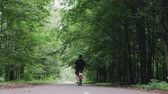 rodas : Rear view of a bearded man in shorts on a vintage red bike, leisurely riding through a forest Park with large deciduous trees. The concept of walking in the fresh air, a healthy lifestyle